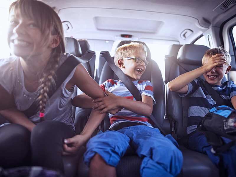 Happy playful kids sitting in the back of car on road trip