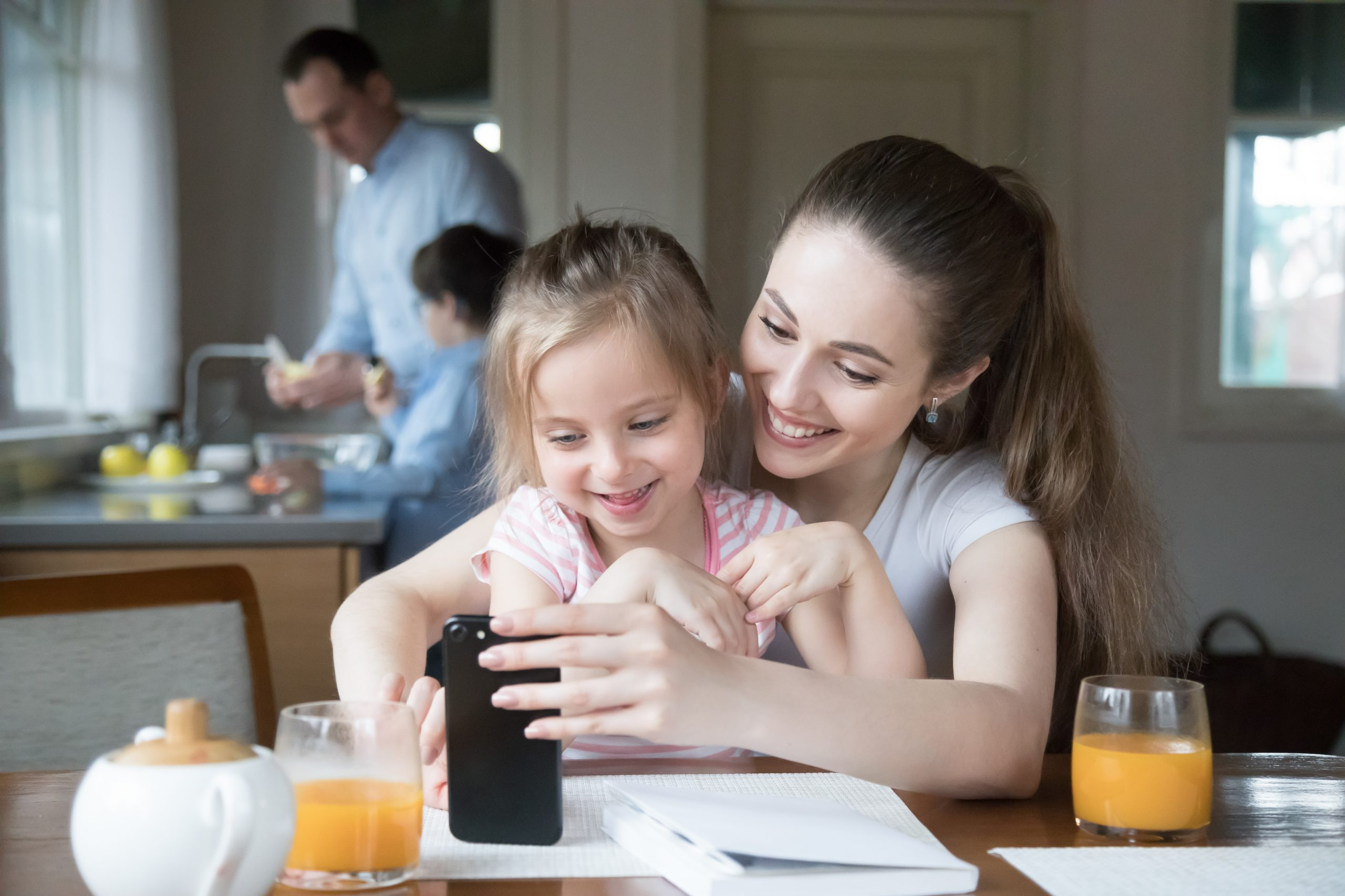 Happy mother and daughter sitting at kitchen table using smartphone